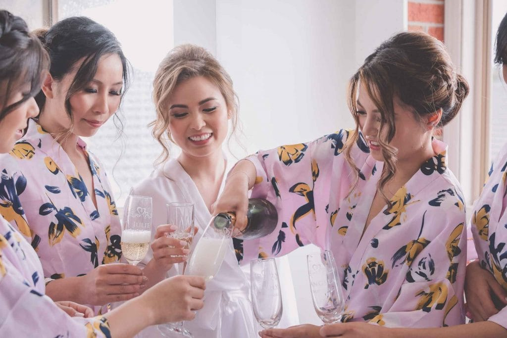 Melbourne wedding photography of the bridal party in robes pouring champagne