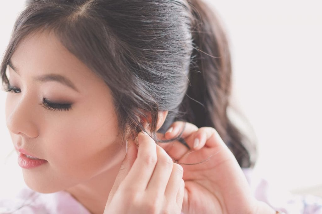 Melbourne wedding photography of a bridesmaid putting on her earrings