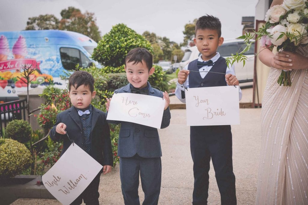 Melbourne wedding photography of three cute nephews with signs announcing the bride's arrival