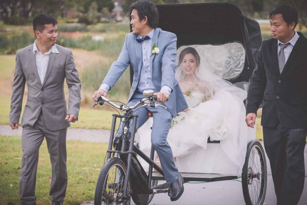 Melbourne wedding photography of the bride arriving at her Asian wedding by rickshaw