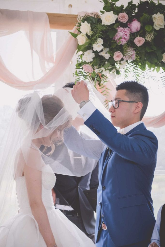 Melbourne wedding photography of a groom lifting his bride's veil