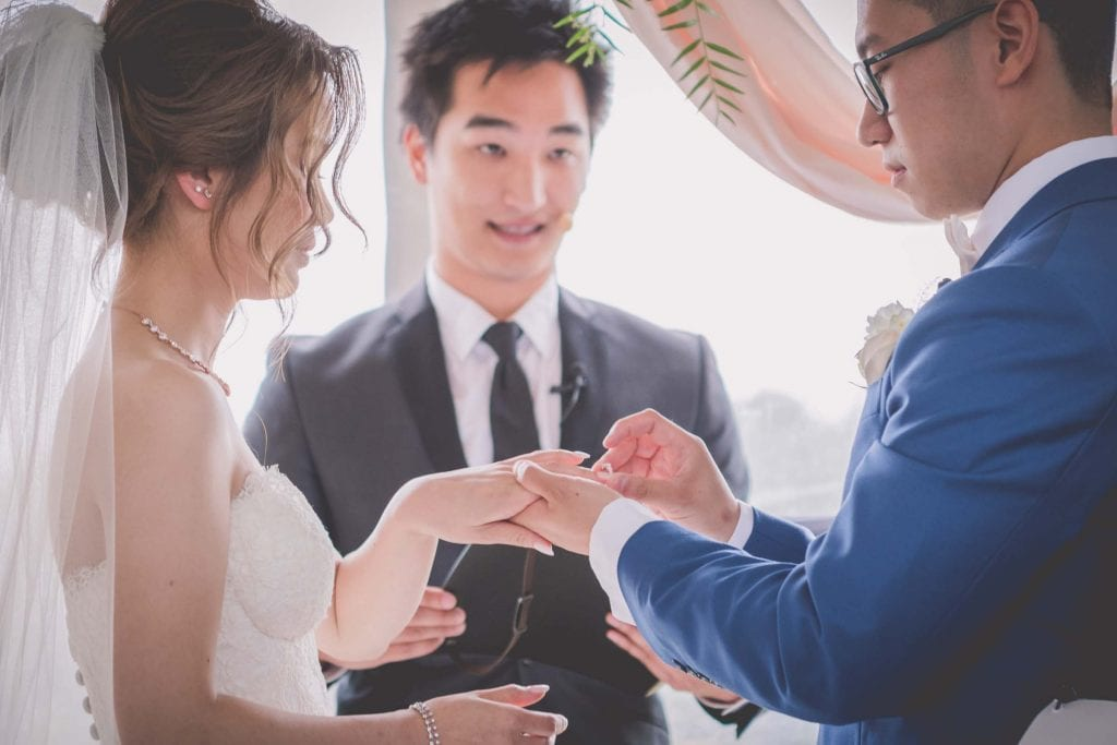 Melbourne wedding photography of the groom placing the ring on his bride's finger