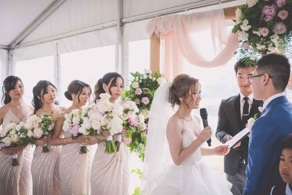 Melbourne wedding photography of the bride reading her vows to her groom with the help of celebrant Jak Nguyen