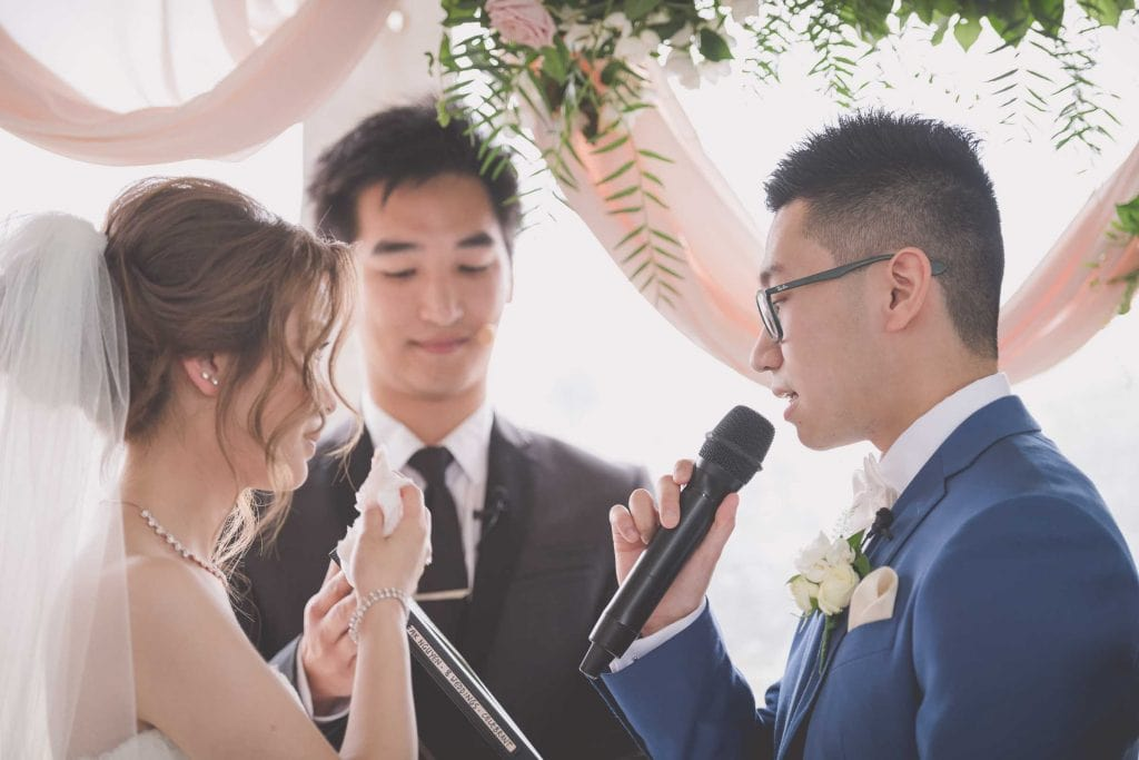Melbourne wedding photography of the groom reading his vows to his bride with the help of celebrant Jak Nguyen