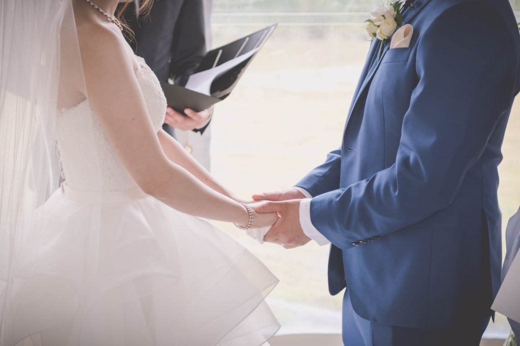 Melbourne wedding photography of the groom and bride's torsos holding hands at the ceremony