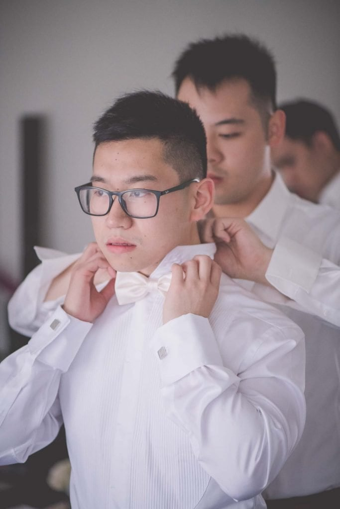 Melbourne wedding photography of a bow tie being fastened