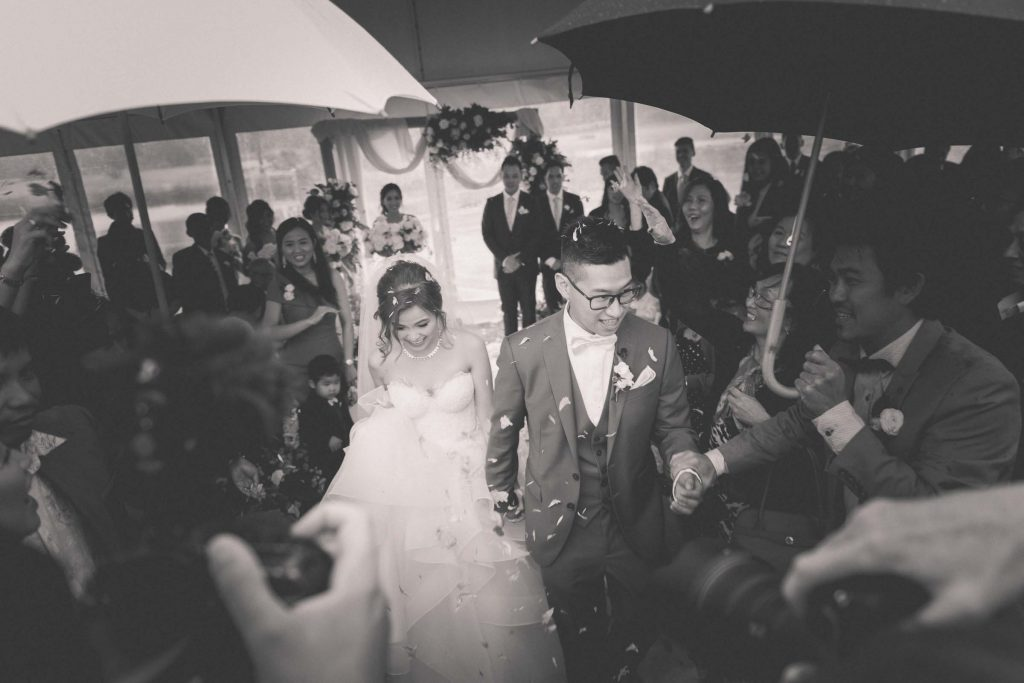 Melbourne wedding photography of flower petals being thrown on the couple in black and white
