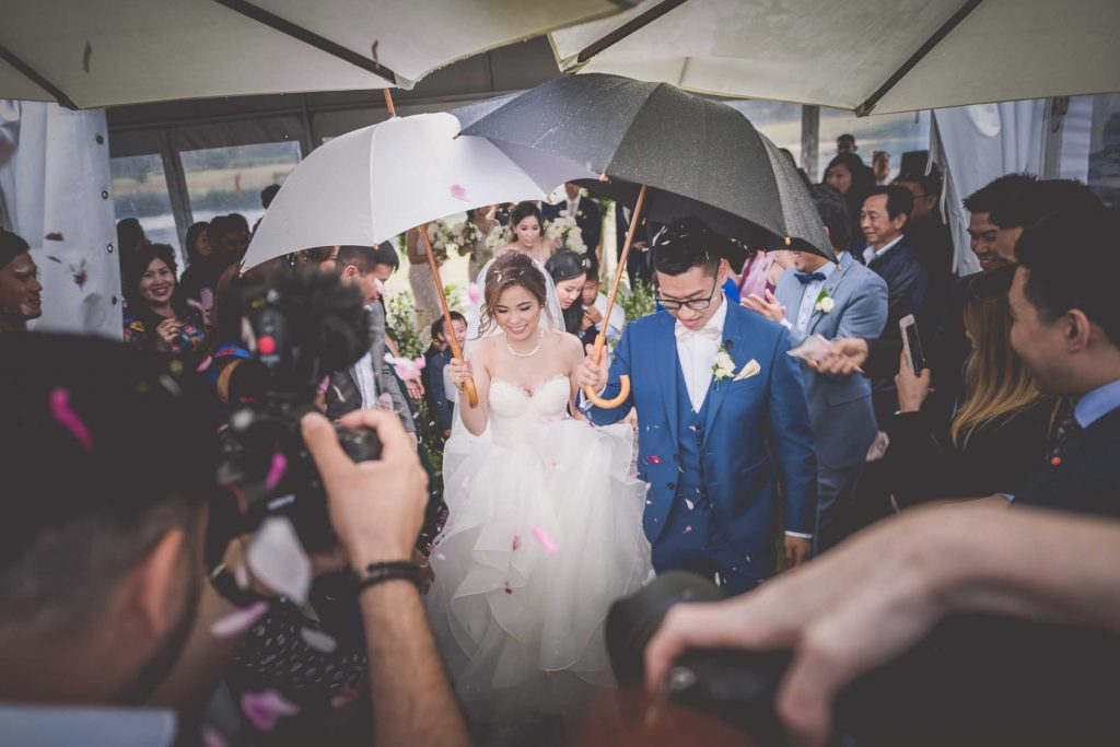 Melbourne wedding photography of flower petals being thrown on the couple as they carry umbrellas