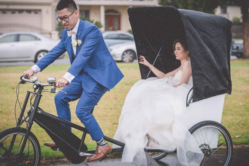 Melbourne wedding photography of a bride being taken on a rickshaw by her new husband in the wet weather