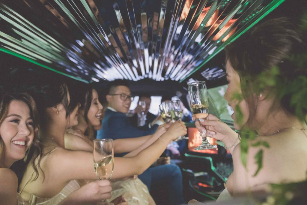 Melbourne wedding photography of the bridal party giving a toast in the limousine