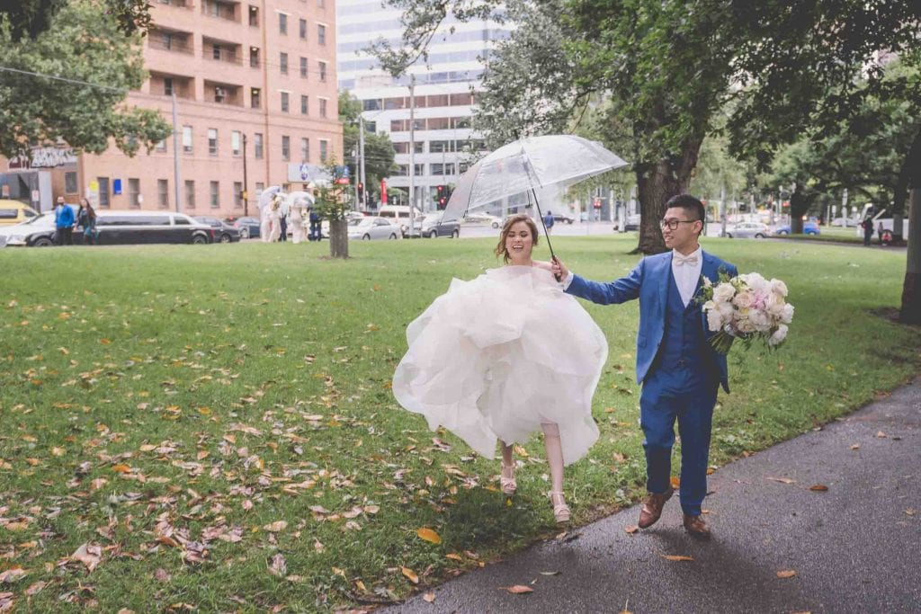 Melbourne wedding photography of the groom helping the bride with an umbrella in Carlton Gardens