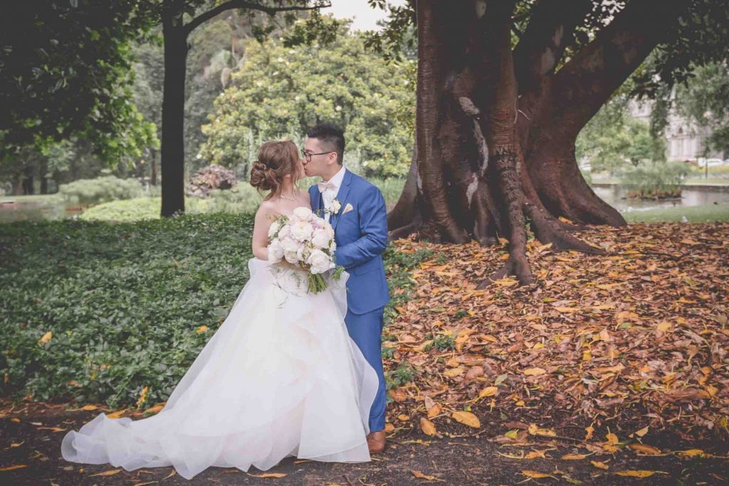 Melbourne wedding photography in Carlton Gardens of the bride and groom kissing under a tree