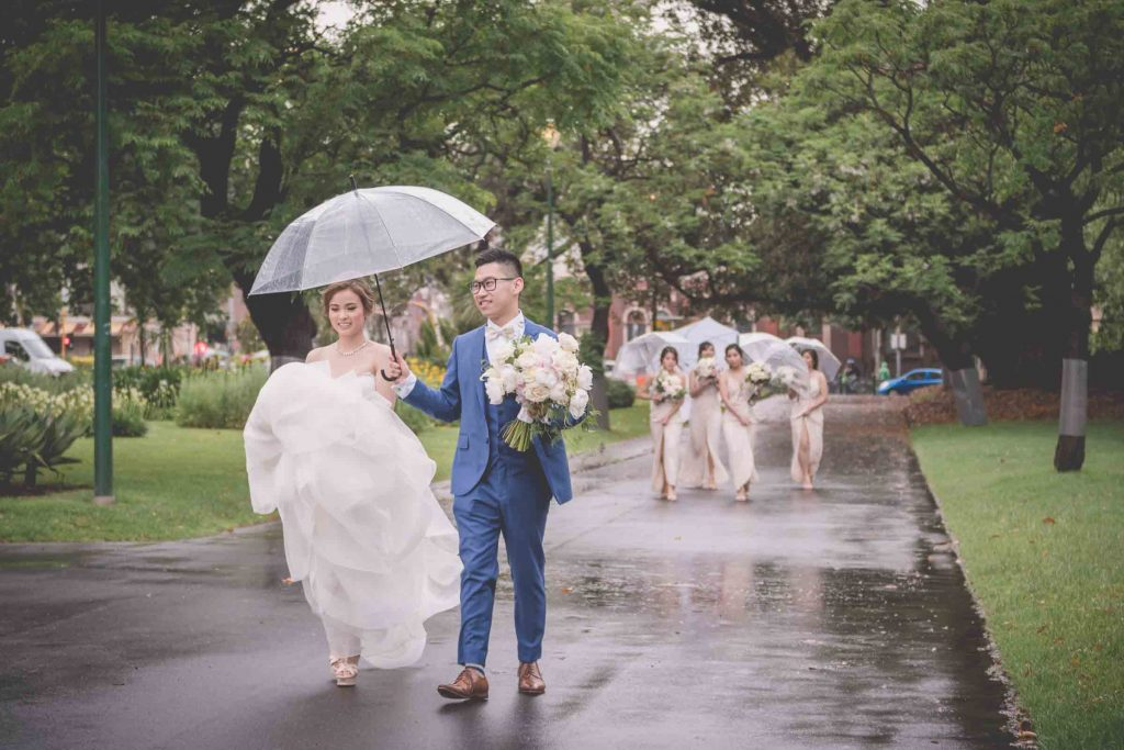 Melbourne wedding photography in Carlton Gardens of the bride and groom walking with bridesmaids following