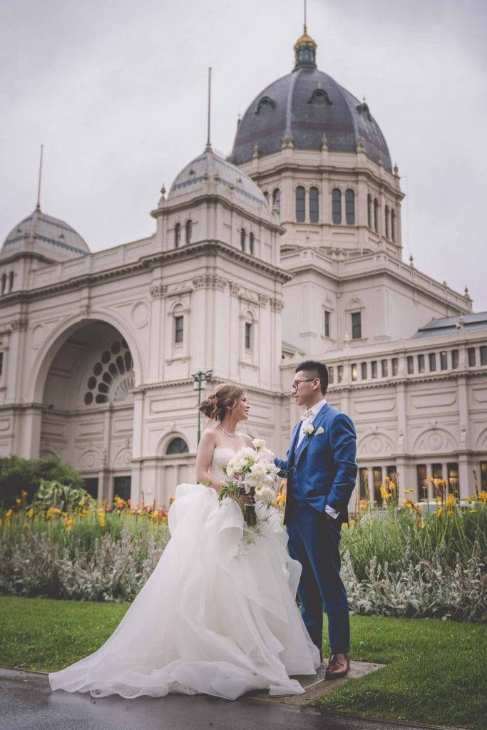 Melbourne wedding photography in Carlton Gardens of the bride and groom beside the palatial Melbourne Exhibition Centre