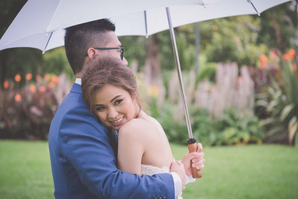 Melbourne wedding photography in Carlton Gardens of the bride with her cheek on the groom's shoulder