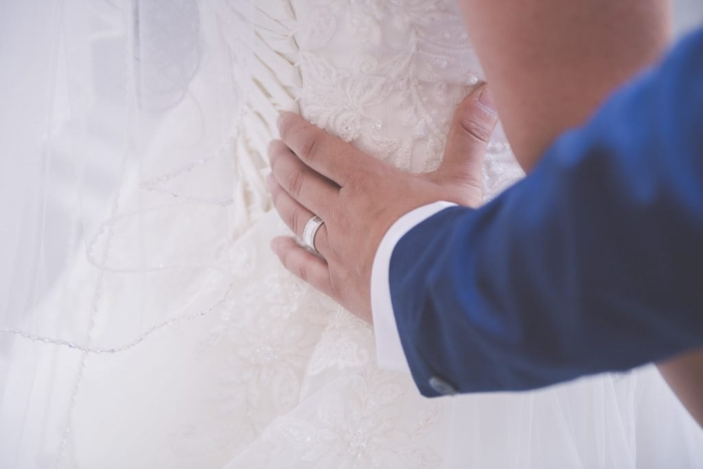 A groom's hand rests on his bride's hip. Artistic Melbourne wedding photography by Pause The Moment