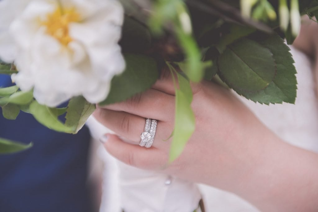 A close up of a bride's hand holding her bouquet, with a focus on her stunning wedding rings.