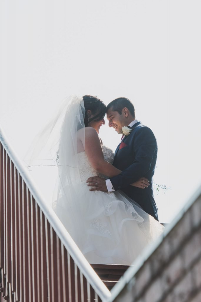 A bride and groom atop a staircase in Richmond. Photography by Pause The Moment