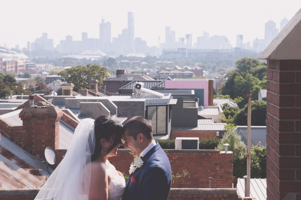 The happy couple embrace out the back of the church, with gorgeous views of the City and the M.C.G.