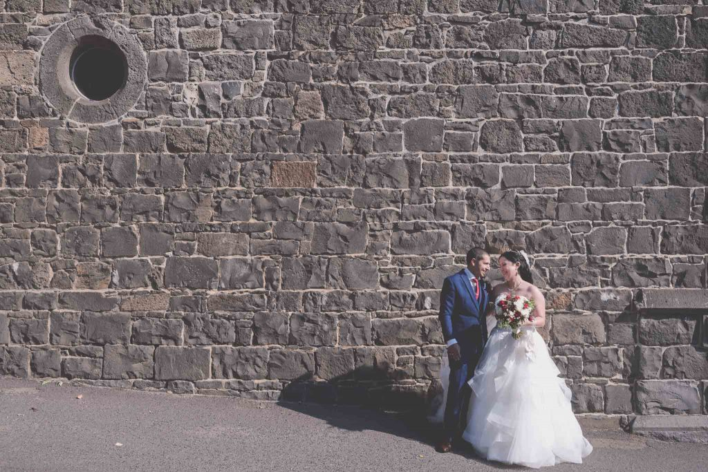 The happy couple stand in front of a bluestone wall.